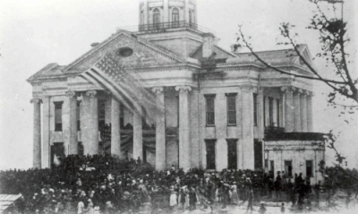 A crowd of largely African Americans mourn the death of President Abraham Lincoln in front of the Warren County Courthouse in Vicksburg, Mississippi, presumably in April 1865.